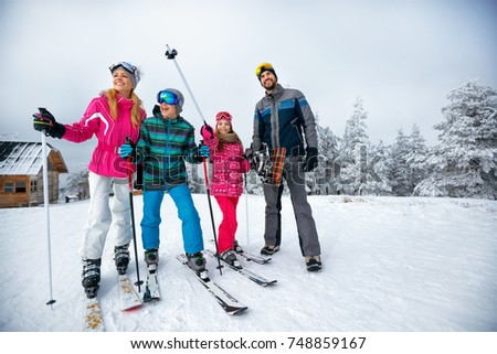 winter time and skiing - happy family with ski and snowboard on on ski have fun