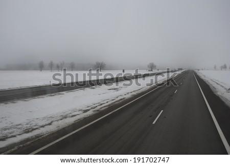 winter time asphalt road and morning mist #191702747