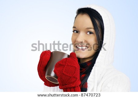 Winter time concept: cute smiling friendly natural young woman with red mittens and white hoodie drinking hot chocolate, coffee or tea in a brown mug over light blue gradient background.