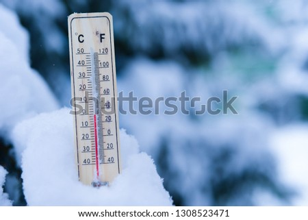 Winter time. thermometer on snow shows low temperatures in celsius or fahreneheit.