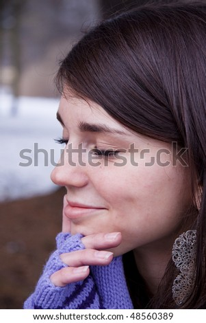 Winter time, thinking young womens face in park.