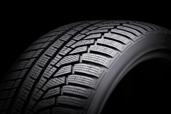 winter tire, driving safety on snowy and icy roads. asymmetric tread pattern. close-up on a black background.