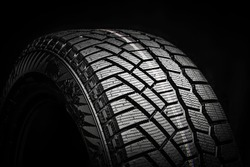 winter tire, friction for snow and ice. asymmetrical tread pattern. close-up on a black background.