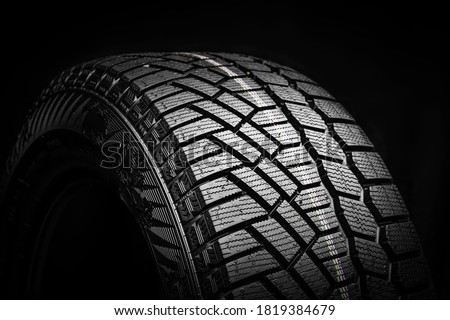 winter tire, friction for snow and ice. asymmetrical tread pattern. close-up on a black background. Foto stock ©