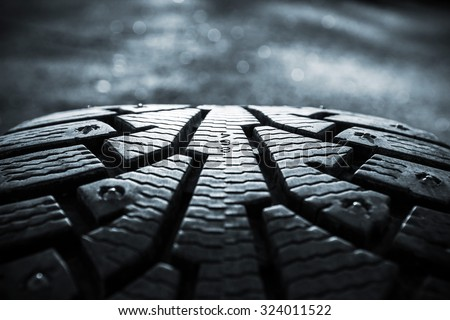Winter tires photographed in close-up view in Finland. Focus point is in the center of the image numbers. The front and back of the image out of focus. Image includes a heavy effect.