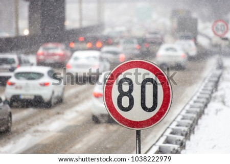 Winter traffic jam during snowstorm with poor visibility. Speed limit sign with a traffic jam in the background on a slippery highway covered with snow #1038222979