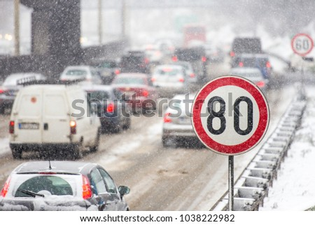 Winter traffic jam during snowstorm with poor visibility. Speed limit sign with a traffic jam in the background on a slippery highway covered with snow #1038222982