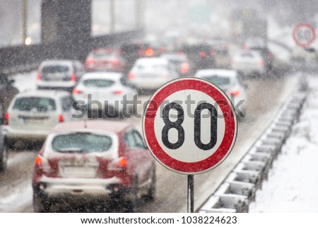Winter traffic jam during snowstorm with poor visibility. Speed limit sign with a traffic jam in the background on a slippery highway covered with snow #1038224623