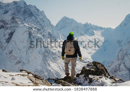 Winter traveler in the mountains. Rocky mountains of Dombai, Caucasus.