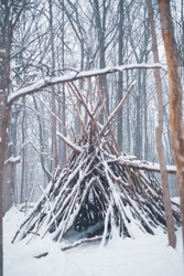 Winter tribal teepee made of sticks. Wooden Native American teepee out in the forest.