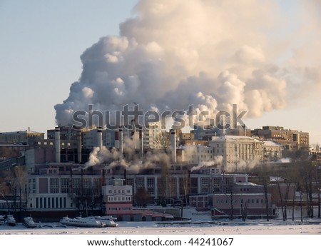 Winter urban landscape. From pipe factory fells smoke into the blue sky.