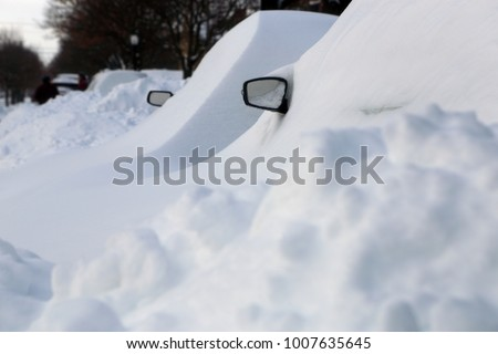 Winter urban scene in Canada. Vehicles covered with snow in the winter blizzard in the parking. Cars in snowdrifts after a snowfall. After the winter storm in Montreal.