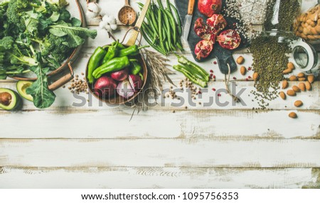 Winter vegetarian, vegan food cooking ingredients. Flat-lay of vegetables, fruit, beans, cereals, kitchen utencil, dried flowers, olive oil over white wooden background, top view, copy space #1095756353