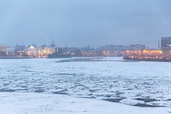Winter view of the Neva River in the city center of St. Petersburg. Cracked ice floes on the surface of the water. Cold winter weather. Near the embankment of the cruiser Aurora. Travel to Russia.