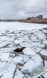 Winter view of the Neva River in the city center of St. Petersburg, Russia. Cracked ice floes on the surface of the water. Cold winter weather. Historical and modern buildings on the embankment.