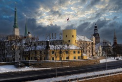 Winter view of the snowy presidential castle and the Dome Cathedral in Riga.