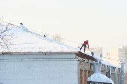 Winter view on man cleaning snow on the roof. Worker in safety suit on roof under snow. Roof snow removal concept. Snow roof cleaning man, snowing weather. Removal work