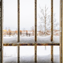 Winter view through a broken prison window with snow covered rusty metal bars