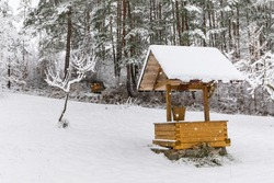 Winter village landscape. Wooden well with a winch in the snowdrifts. Old rural well in winter near the forest. Drinking water.