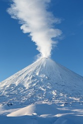 Winter volcanic landscape: highest active volcano of Eurasia - Klyuchevskoy Volcano (Klyuchevskaya Sopka), view of top of volcanic eruption: emission from crater plume of gas, steam and ashes.