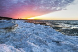 Winter Weather Background.  Snow and ice on the Great Lakes on a cold winter day with a sunset background. Port Crescent State Park. Port Austin, Michigan.