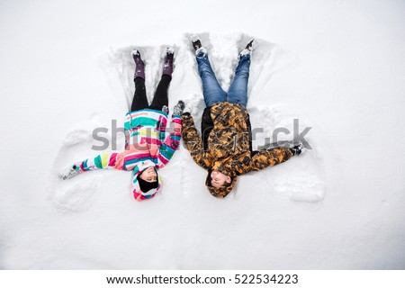 Winter weekend, couple in love having fun on snow in snowfall weather