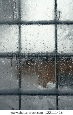 Winter window, drops of water and snowflakes on a window pane.