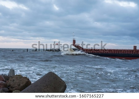 Winter with windy Baltic sea and cargo ship near the port of Ventspils in Latvia
