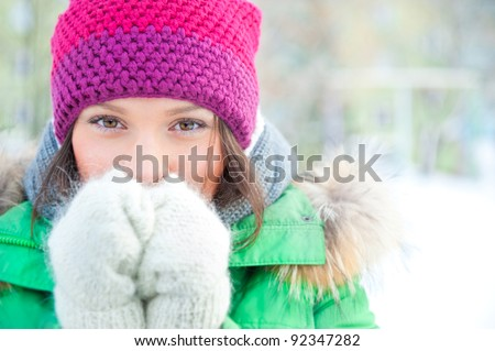Winter woman in snow looking at camera outside on snowing cold winter day. Portrait Caucasian female model outside in first snow