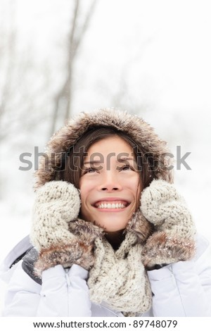 winter woman in snow looking up at copy space outside on snowing cold winter day. Portrait multiethnic Caucasian Asian female model outside in first snow