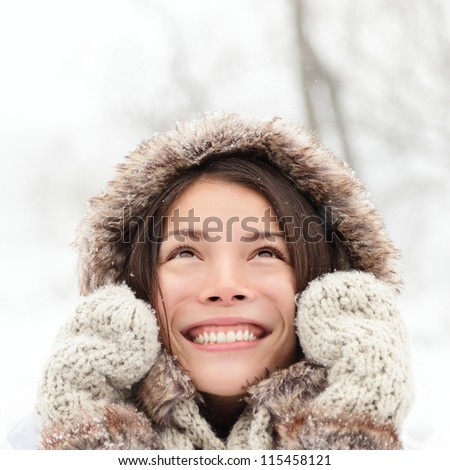 Winter woman looking up happy and smiling outdoors in snow on cold winter day. Asian girl model in her twenties.