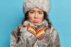 Winter woman looks sadly at camera feels cold dressed in grey fur hat and coat warm knitted mittens dressed for wintry weather isolated over blue background. Displeased arctic lady from north