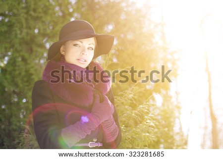 Winter woman on background of winter landscape, sun. Fashion girl in forest wonderland. Winter sunset scene. Model in sunlight, backlight