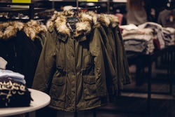 Winter women clothes in clothing store. Women's winter parka with a fur hood in the women's clothing store ready for sale