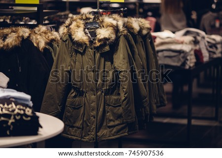 Winter women clothes in clothing store. Women's winter parka with a fur hood in the women's clothing store ready for sale - Shutterstock ID 745907536