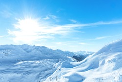 Winter wonder land with a ski park - a beautiful mountain landscape with a amazing blue sky. The sun is shining and the hills are covered with snow like the alps, himalaya ore the rockymountains