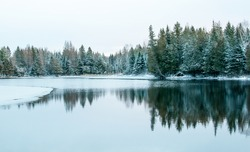 Winter wonderland, frozen lake with reflection of trees in water - Mont-Tremblant, Quebec, Canada