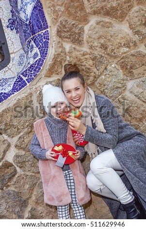 Winter wonderland in Barcelona at Christmas. elegant mother and child travellers in a Santa hat at Guell Park in Barcelona, Spain eating traditional king cake #511629946