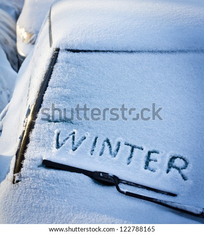Winter written in snow on car windscreen below windscreen wiper