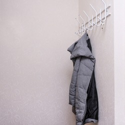Wintercoat hanging on a hook in a corridor, hallway at the entrance.