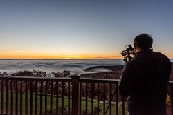 Wintergreen, Virginia ski resort town village with clouds fog mist inversion in Blue Ridge mountains at sunrise and man with camera photographer on apartment balcony