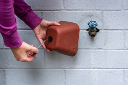 Winterization, woman's hands installing foam and plastic faucet cover to prevent pipes freezing, on a blue gray painted brick wall