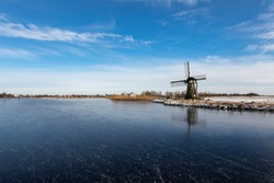 Winterlandscape with ice on the Dieperpoel (Kagerplassen) in front of a windmill (de Kok) and house on the Kogjespolder in the south-holland municipality of Teylingen (Sassenheim) in the Netherlands.