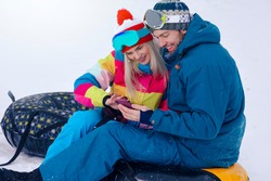 Wintersport Activities. Lovely Caucasian Couple Having Tube Activities In Winter Time And Posing Together And Checking Selfie Outdoor. Horizontal Image