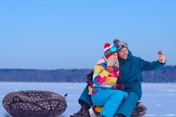Wintersport Activities. Lovely Caucasian Couple Having Tube Activities In Winter Time And Posing Together For Taking Selfie Outdoor. Horizontal Image