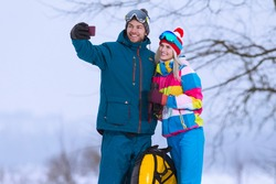Wintersport Activities. Lovely Caucasian Couple Having Tube Activities In Winter Time And Posing Together For Taking Selfie In Mountains. Horizontal Image