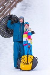 Wintersport Activities. Lovely Caucasian Couple Having Tube Activities In Winter Time And Posing Together In Mountains. Vertical Composition