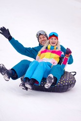 Wintersport Activities. Lovely Caucasian Couple Having Tube Activities In Winter Time And Sliding Downhill In Mountains. Vertical Image