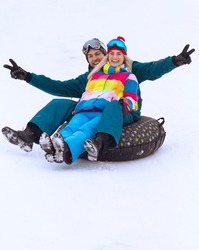 Wintersport Activities. Lovely Caucasian Couple Having Tube Activities In Winter Time And Sliding Downhill In Mountains. Square Image