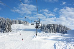 Wintersports fans riding the ski lift to empty pastes in the Alpine ski resort of Avoriaz.